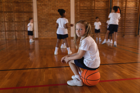 Side view of schoolgirl sitting on basketball and looking at camera at basketball court in school Imagens