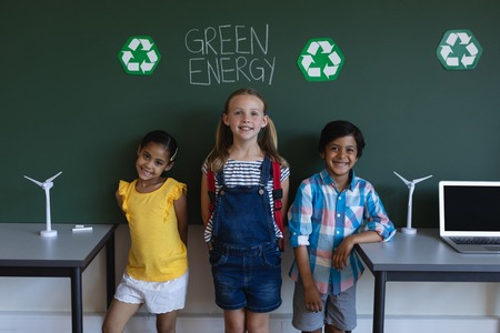 Front view of smiling schoolkids standing against green energy board in classroom of elementary school