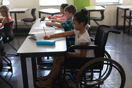 Side view of disabled schoolgirl with classmates studying and sitting at desk in classroom of elementary school 写真素材