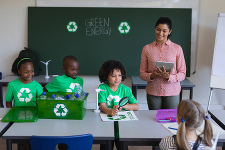 Front view of schoolkids studying about green energy and recycle at desk in classroom of elementary school
