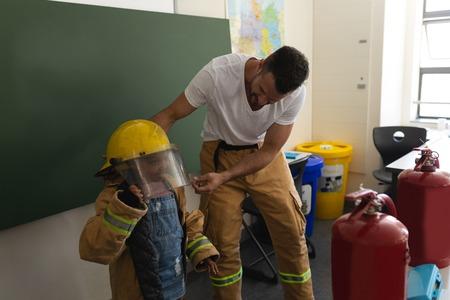 Male Caucasian firefighter help to wearing fire uniform to a black schoolgirl in classroom of elementary school