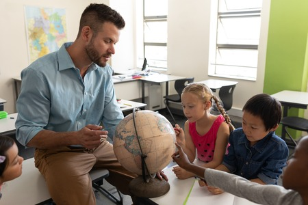 Side view of male teacher teaching his kids about geography by using globe in classroom of elementary school