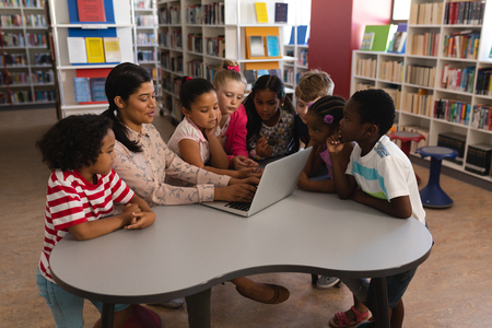 Side view of female teacher teaching curious schoolkids on laptop at table in school library