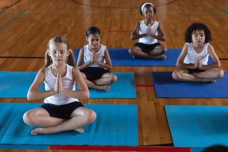 Vorderansicht von Schulkindern, die Yoga machen und auf einer Yogamatte in der Schule meditieren