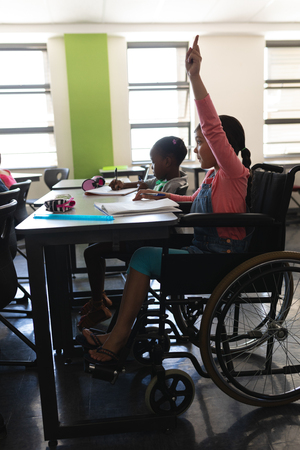 Side view of disable schoolgirl raising hand and sitting at desk in classroom of elementary school