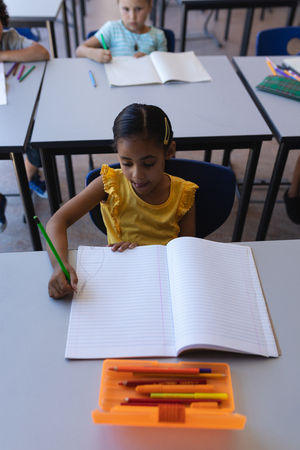 High angle view of schoolgirl writing on notebook at desk in classroom of elementary school