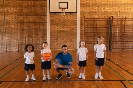 Front view of happy basketball coach and schoolkids looking at camera at basketball court