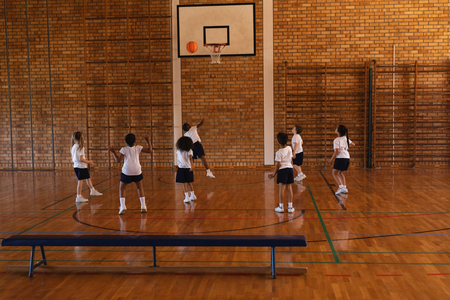 Rear view of schoolkids playing basketball at basketball court in school 写真素材