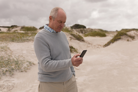 Side view of active senior man using mobile phone at the beach. He seems happy