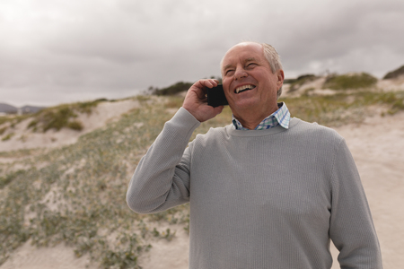 Front view of active senior man talking on mobile phone at beach. She seems happy Stok Fotoğraf