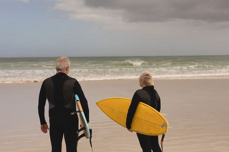 Rear view of senior couple standing with surfboard on the beach