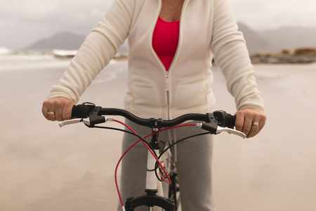 Mid section of senior woman riding a bicycle on the beach against mountains in the background