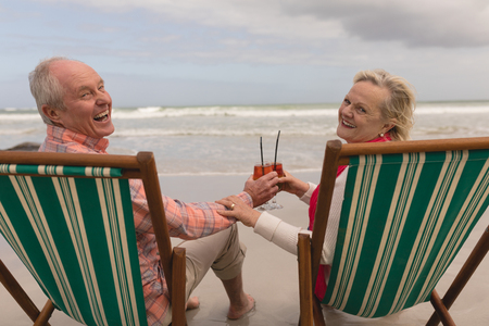 Back view of active senior couple toasting glasses of cocktail drinks in a sun lounger at the beach with ocean in the background. They seem happy
