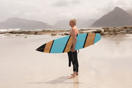 Side view of a thoughtful senior man standing with surfboard on the beach against rocks in the background Stock Photo