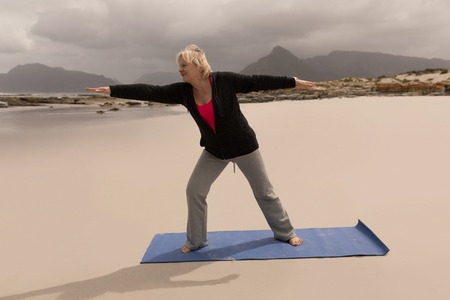Front view of active senior woman performing stretching exercise on a yoga mate on the beach