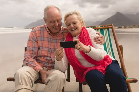 Active senior couple using mobile phone while relaxing in a sun lounger on the beach Foto de archivo
