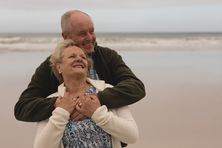 Front view of active senior couple embracing standing at the beach with ocean in the bacground. They seem happy