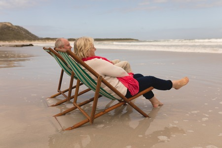 High angle view of active senior couple relaxing in a sun lounger on the beach Standard-Bild