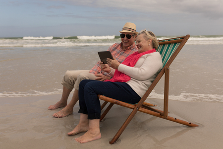 Side view of active senior couple using digital tablet while relaxing in a sun lounger at the beach with ocean in the background. They seem happy
