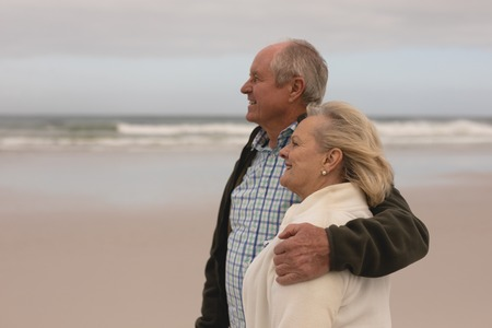 Side view of happy active senior couple standing with arm around at the beach with ocean in the background. They seem happy