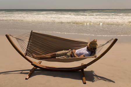 High angle view of young man with hat and hand behind hand relaxing on hammock at beach in the sunshine