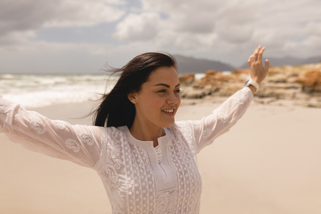 Front view of happy young woman with arms stretched out standing on beach in the sunshine Imagens