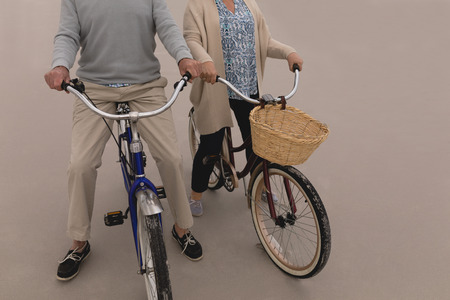 Low section of active senior couple riding a bicycle on the sand at the beach. They seem happy Banco de Imagens