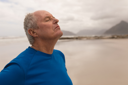 Side view of a senior man closing his eyes on the beach