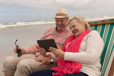 Side view of active senior couple using digital tablet while relaxing in a sun lounger at the beach with ocean in the background. They seem happy Banco de Imagens