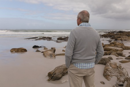 Rear view of active senior man standing with hands in pocket at beach Stock Photo