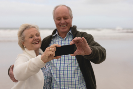 Front view of active senior couple taking selfie with mobile phone standing at the beach with ocean in the background. They seem happy Banco de Imagens - 121688041