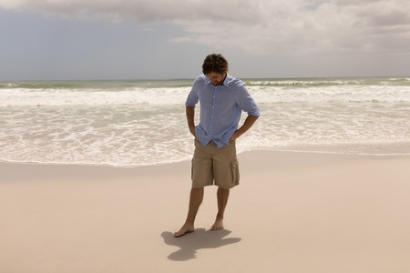 Front view of a thoughtful man standing on the beach
