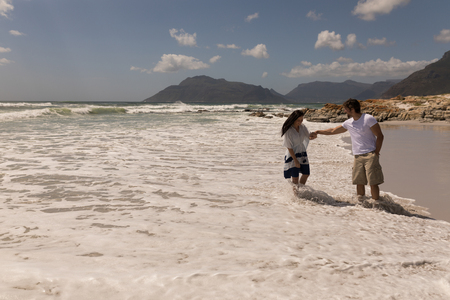 Front view of young couple holding hands and having fun at beach in the sunshine Banco de Imagens