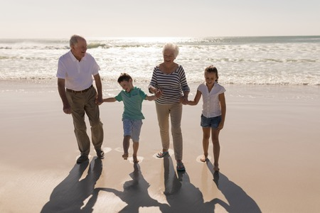Front view of happy multi-generation family holding hands and standing on beach in the sunshine
