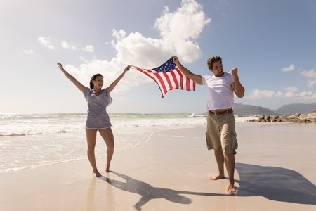 Front view of happy young couple holding american flag and having fun on beach in the sunshine