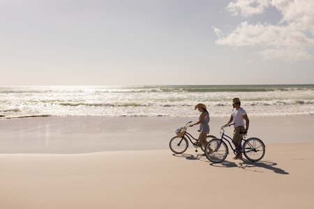 Side view of young couple with bicycle standing on beach in the sunshine