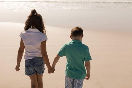 Rückansicht von Geschwistern, die Händchen halten und im Sonnenschein am Strand spazieren gehen