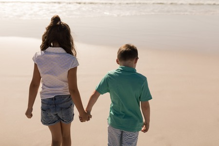 Rear view of siblings holding hands and walking on beach in the sunshine