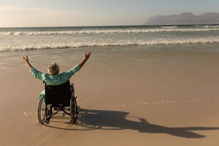 Rear view of disabled senior man with arms outstretched on the beach Stok Fotoğraf