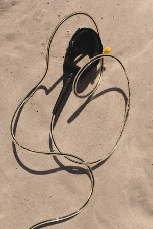 Close-up of surfboard leash on beach in the sunshine