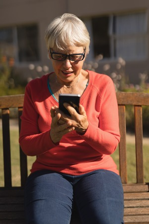 Front view of an active senior Caucasian woman using mobile phone in the park