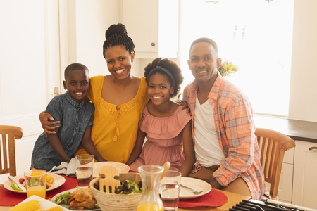 Front view of happy African American family looking at camera in dining room in their comfortable home Stock Photo