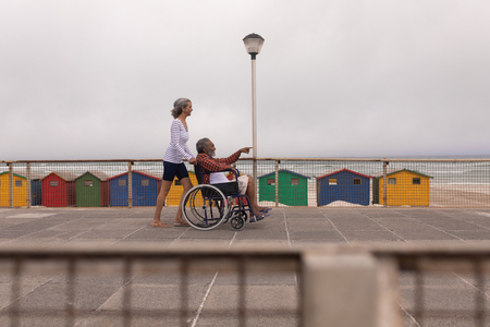 Side view of disabled senior man and senior woman walking on promenade at beach
