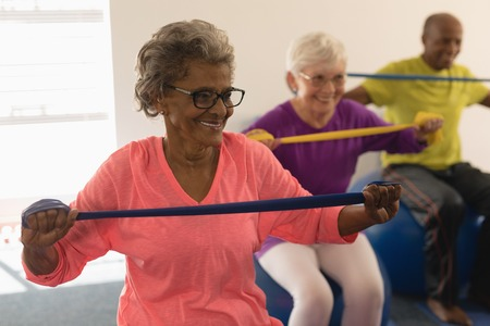 Happy senior woman exercising with resistance band in fitness studio 스톡 콘텐츠