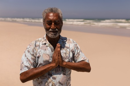 Front view of senior black man with hands clasped praying on beach in the sunshine