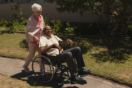 Front view of senior woman pushing senior man in a wheelchair on sunny day at park