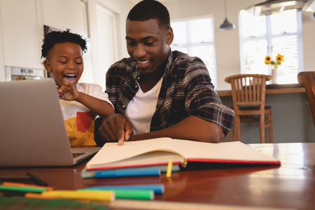 Front view of African American father helping his son with homework with his computer at table Stock Photo