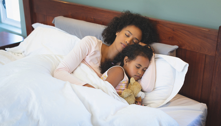 High angle view of African American mother and daughter sleeping together on bed in bedroom at home Stock Photo