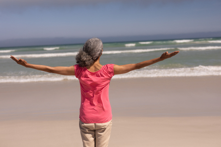 Rear view of senior woman with arms stretched out standing on beach in the sunshine Imagens