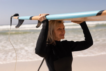 Side view of active senior female surfer carrying surfboard on her head at beach